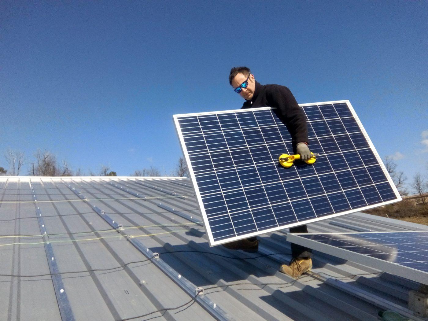 Photo : installation de panneaux PV sur le toit de la centrale du Mas de l'Escarida (36 kWc)