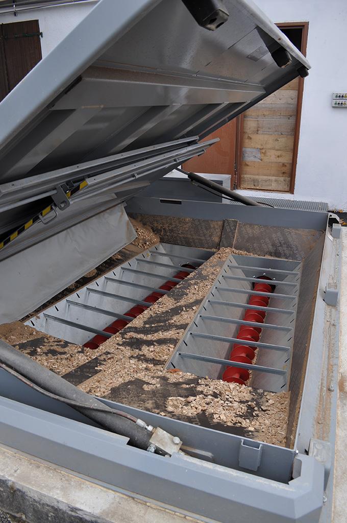 Trappe à déversement des plaquettes bois, avec les deux vis sans fin qui les transportent jusqu'au local de stockage des plaquettes