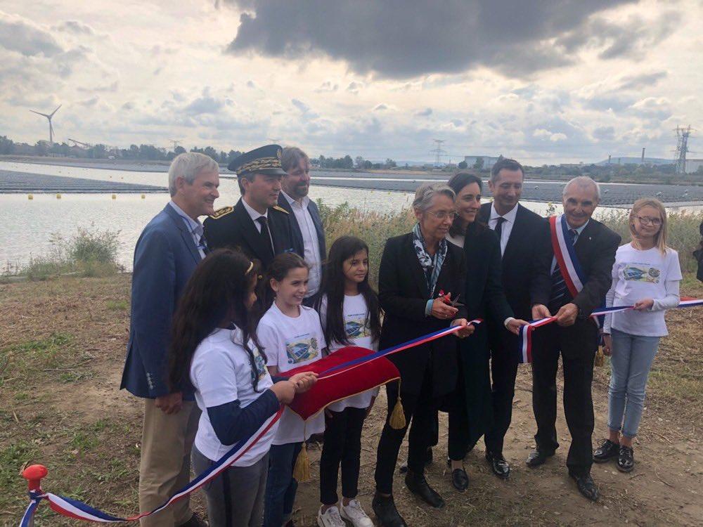 Élisabeth Borne, Brune Poirson, le maire de Piolenc Louis Driey et des enfants de l'école municipale coupent le ruban lors de l'inauguration de la centrale solaire flottante O'MEGA1