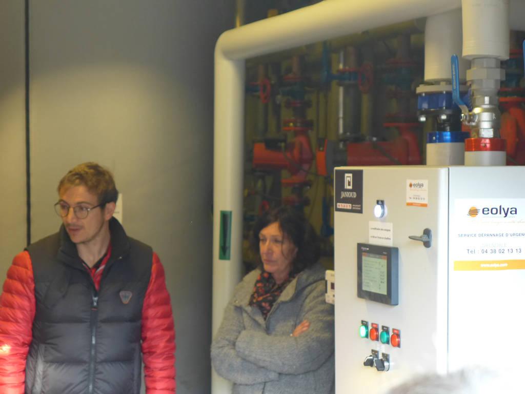 Robin Gaillard de la société Eolya, chargée de l'exploitation et de la maintenance, présente la sous-station du réseau de chaleur à l'intérieur de l'école des Pies.