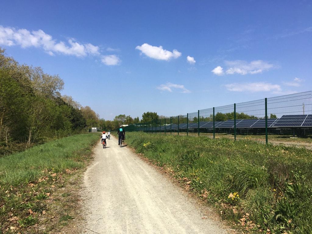 Des cyclistes passent à côté de la centrale photovoltaïque sur le chemin de La Loire à vélo